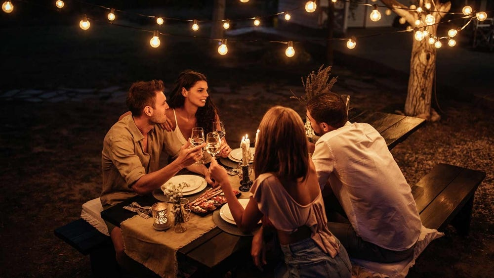 A couple having dinner with their friends to celebrate their wedding.