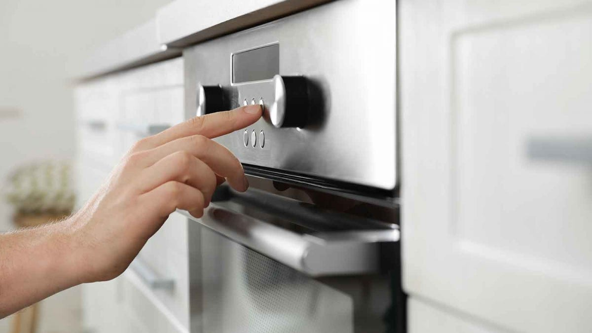 Person activating the self-cleaning cycle on their oven