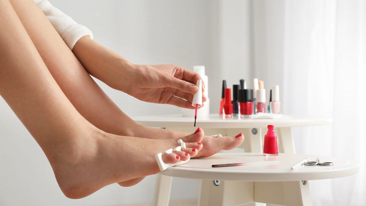 Woman painting her toenails during a home pedicure.