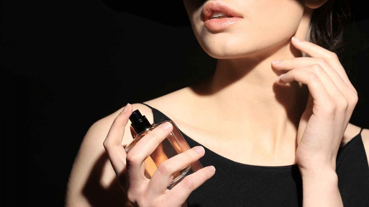 Woman spritzing perfume on her neck against a black background.