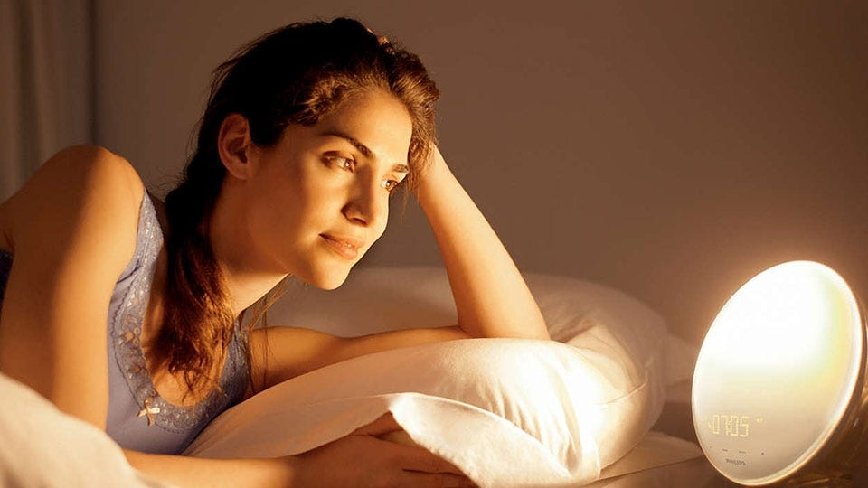 Woman waking up in the early morning with a sunrise alarm clock.