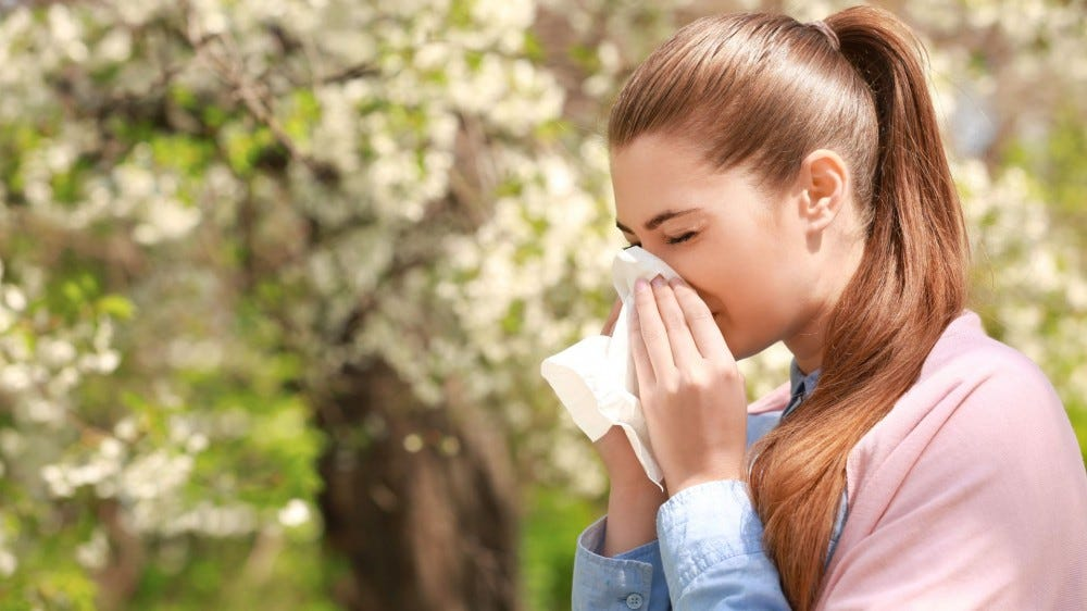 A woman blows her nose with a tissue next to a tree.