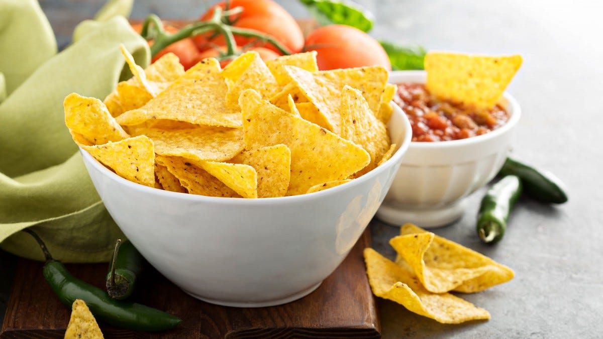 A bowl of homemade tortilla chips with salsa.