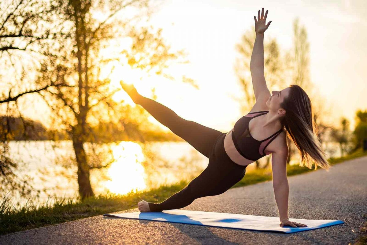 Woman doing yoga in the park at sunrise