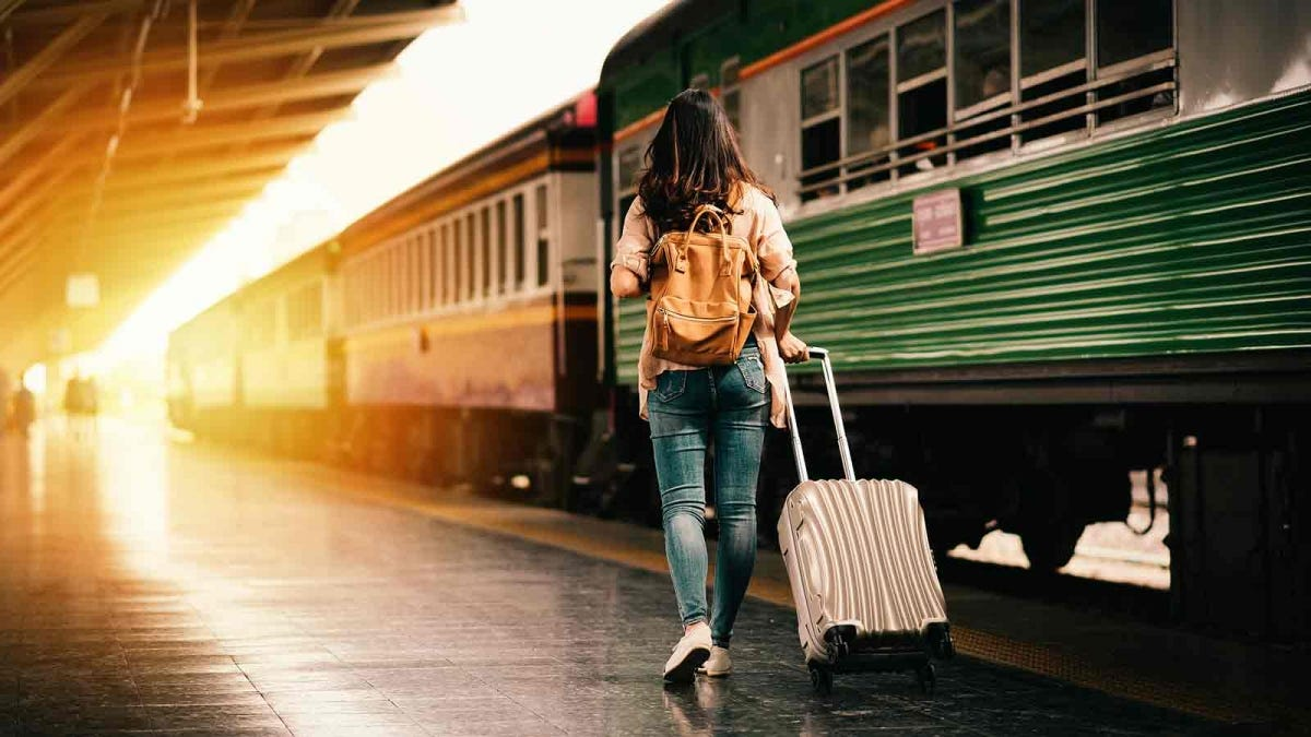 Woman with her luggage walking alongside a train at the station.