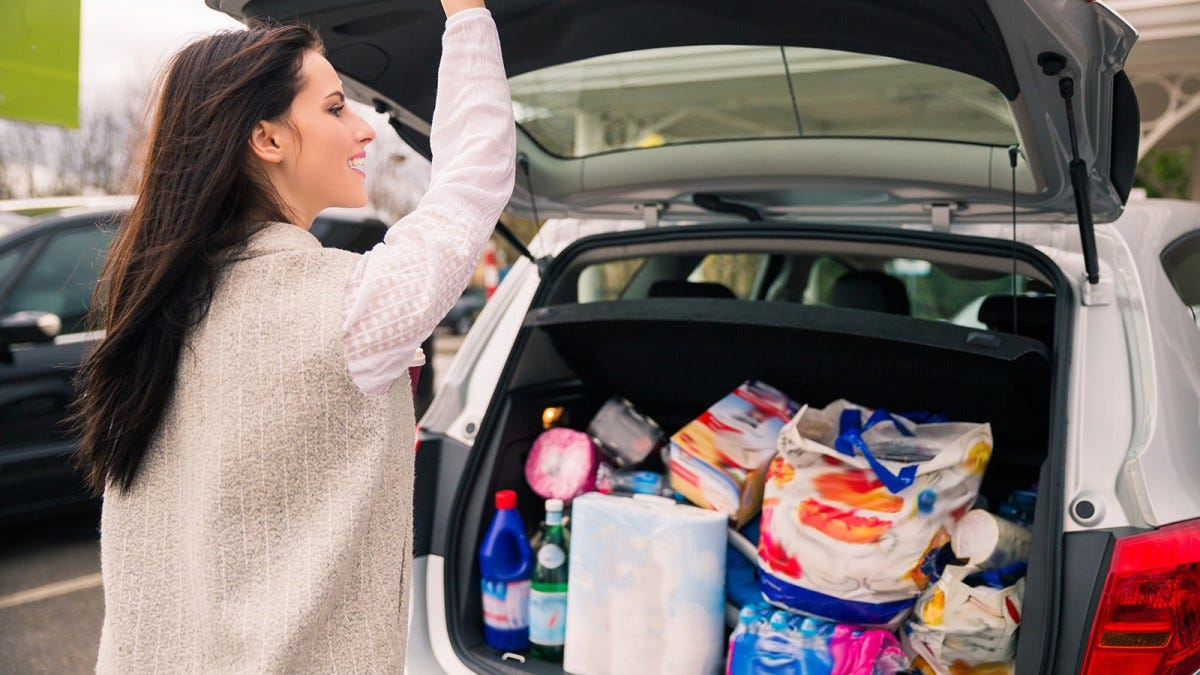 A woman getting ready to close the door on a trunk full of groceries.