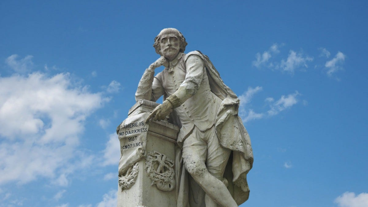A statue of William Shakespeare, against a background of blue skies and wispy clouds.
