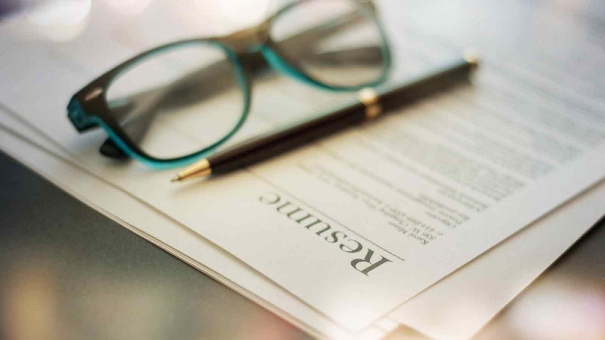 Resume sitting on a table with reading glasses and a pen on top of it.