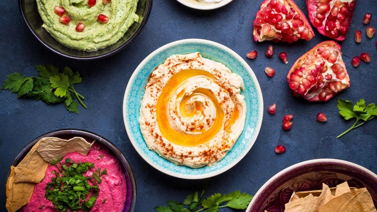Delicious bowls of different kinds of hummus on a blue table.