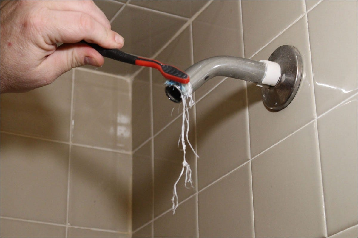 Use a toothbrush to clean the threads on the shower arm.