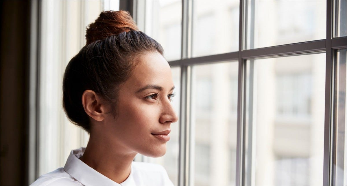 Young businesswoman with hair bun looking out of window