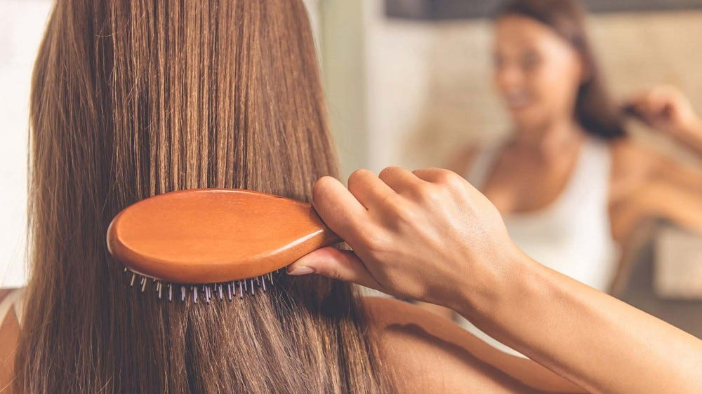A woman looking in a mirror as she brushes her hair.