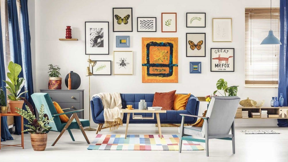 A sunny living room with a large gallery wall of photos and prints.