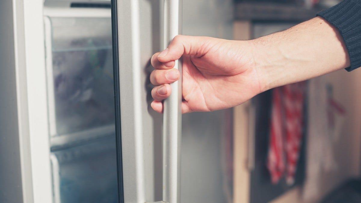 Man opening the freezer to put food away.