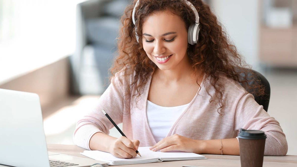 young woman listening to headphones while filling in her paper calendar