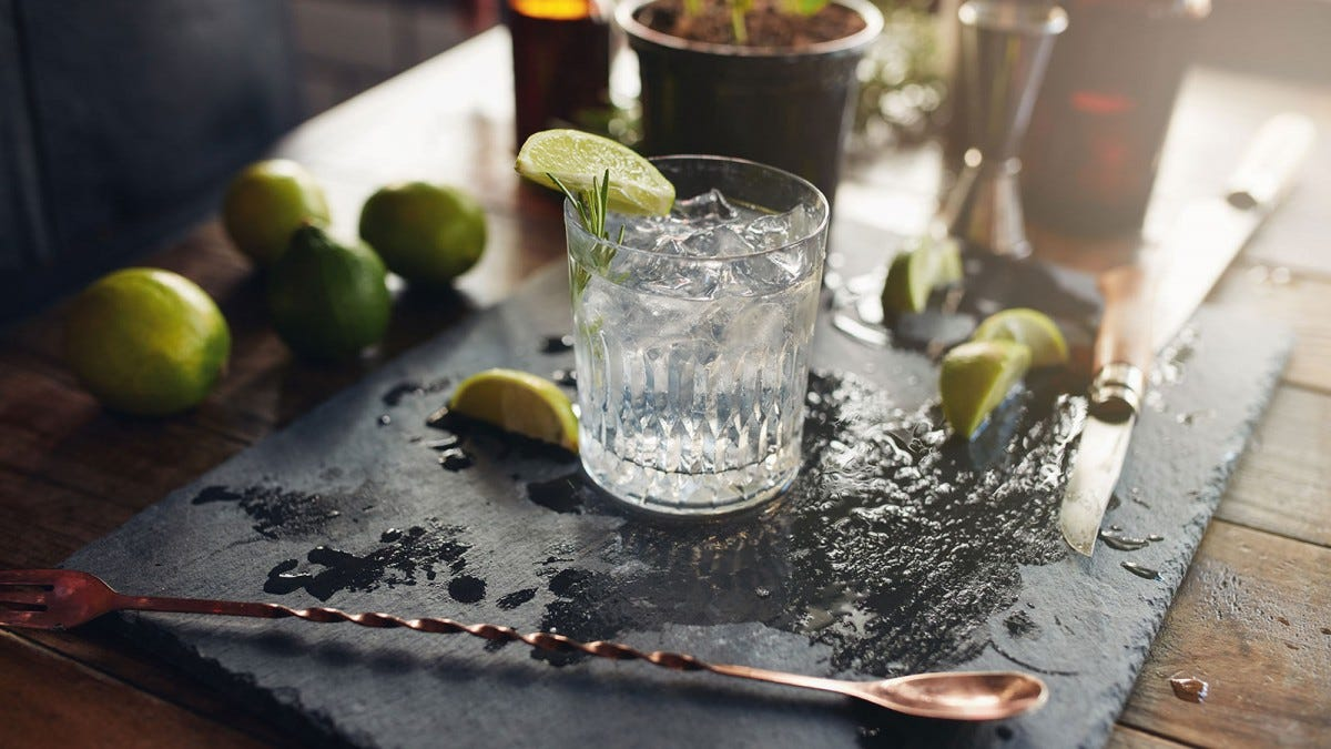 A gin and tonic in a glass on a slate cutting board surrounded by limes.
