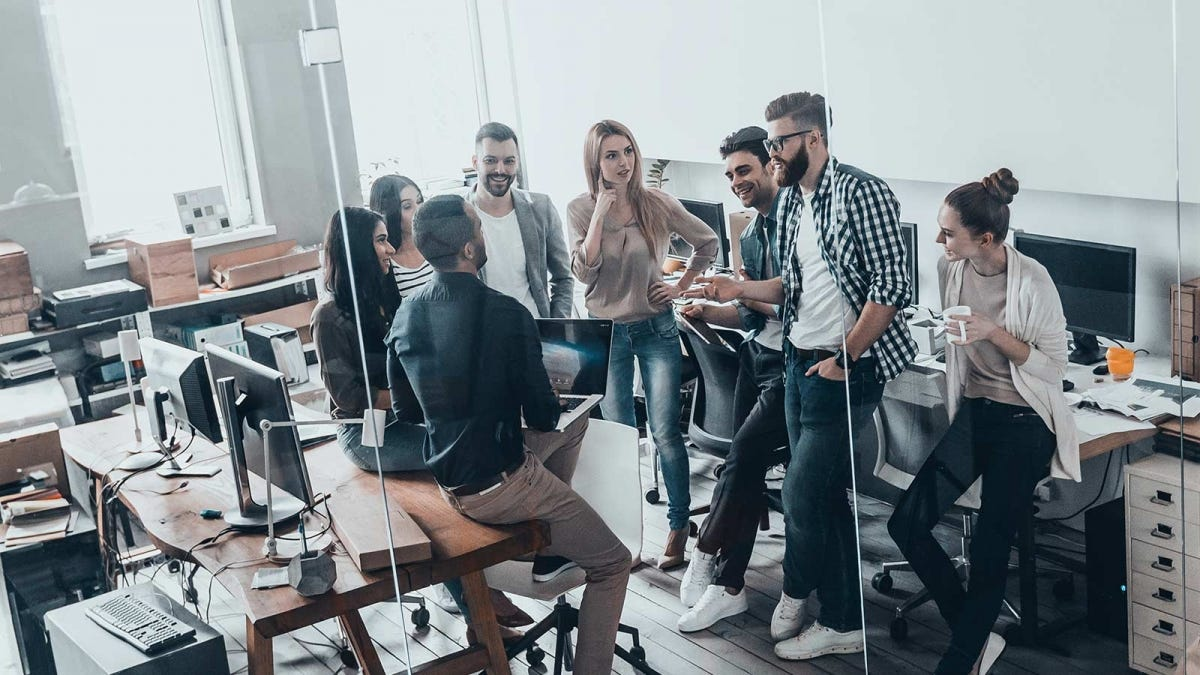 A group of people standing and chatting in an office work space.