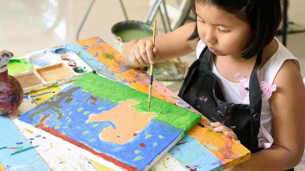 A young girl painting a picture.