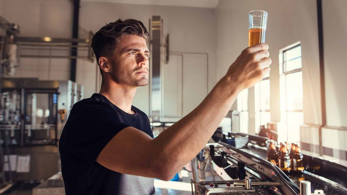 Man examining freshly brewed beer