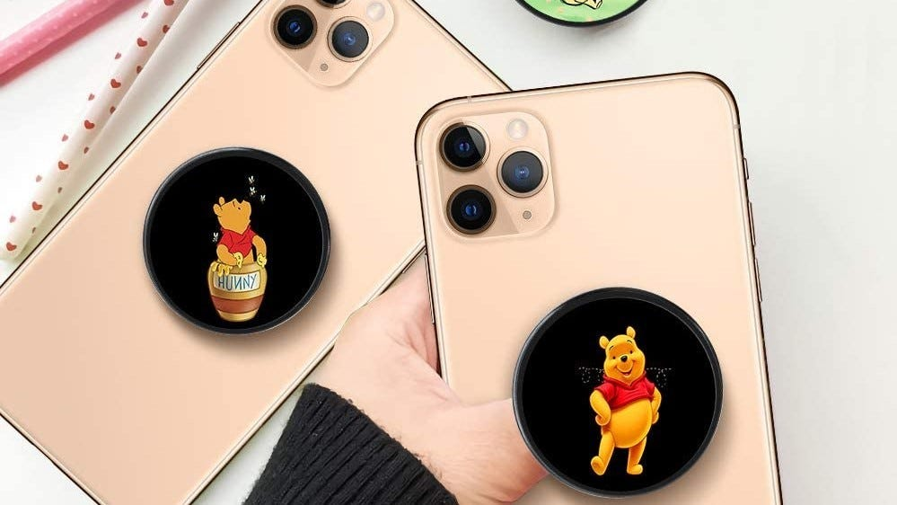 Two phones with Winnie the Pooh PopSockets on them.