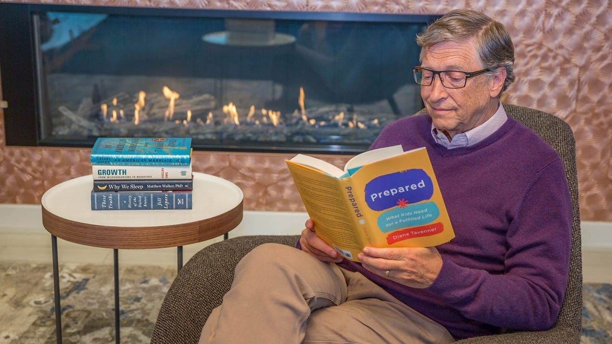 Bill Gates sitting in a chair and reading a book by a fireplace.