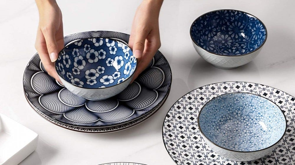 Person setting a table with blue soup bowls.