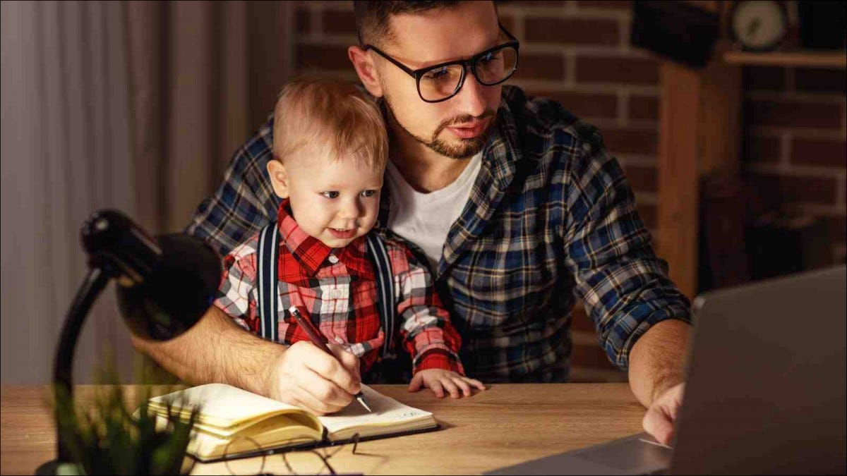 father working at home while holding son