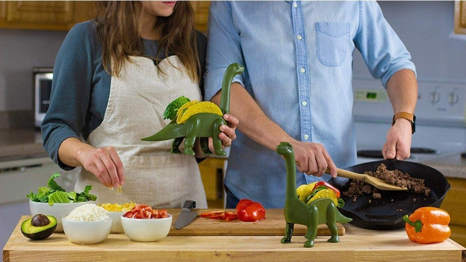 A young couple preparing dinner on Taco Tuesday night using their new dinosaur taco holders. The male is preparing taco meat while the female starts filling the shells with fresh veggies and cheese.