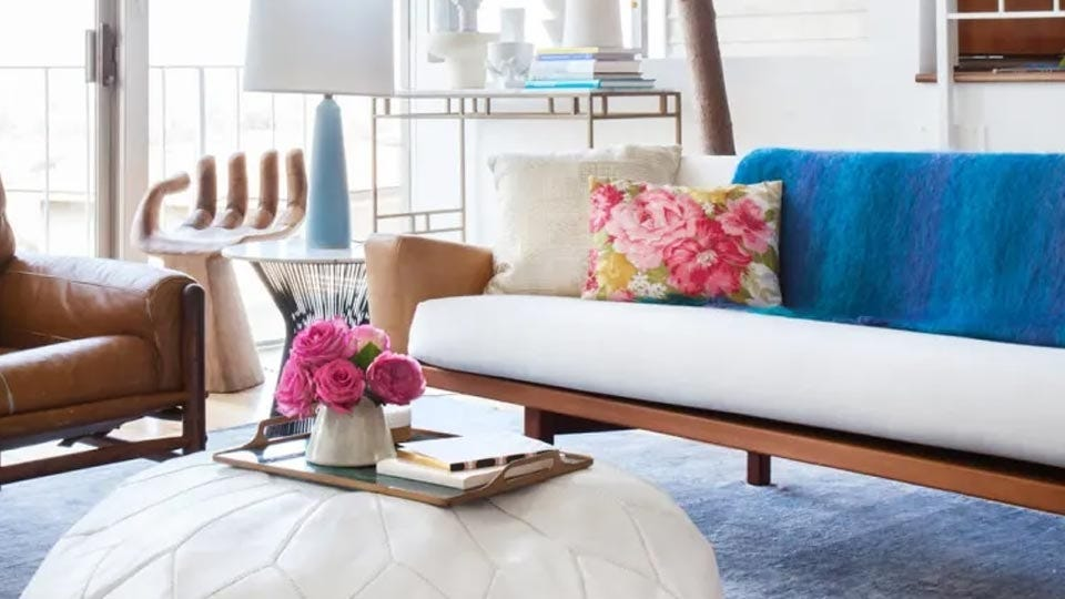 A beautifully decorated living room with a blue throw blanket over the back of the white couch.