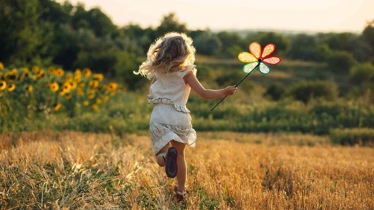 girl running in a wheat field with a pinwheel