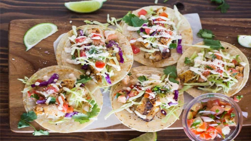A cutting board topped with five fish tacos, each drizzled with a freshly made crema sauce with pico de gallo and limes on the side.