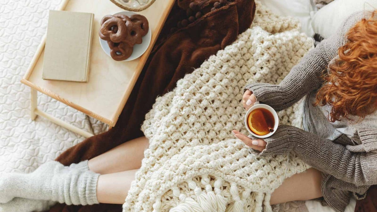 Woman snuggled up under a blanket with a cup of tea.