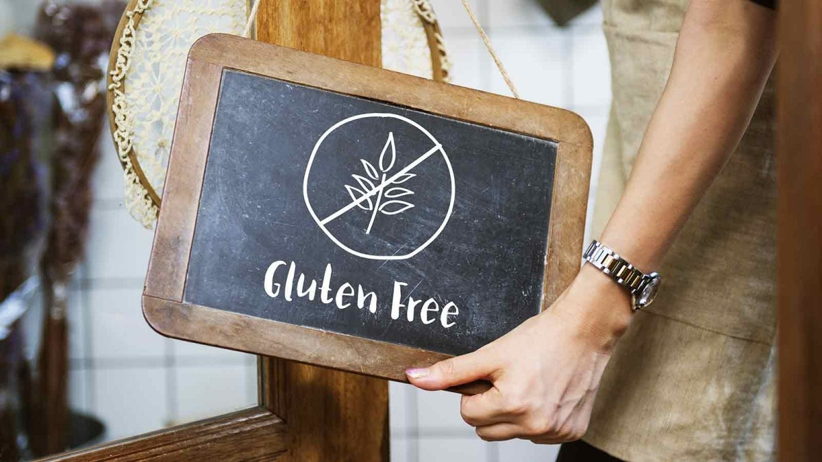 "Sign hanging on the door of a bakery that reads ""Gluten Free"""