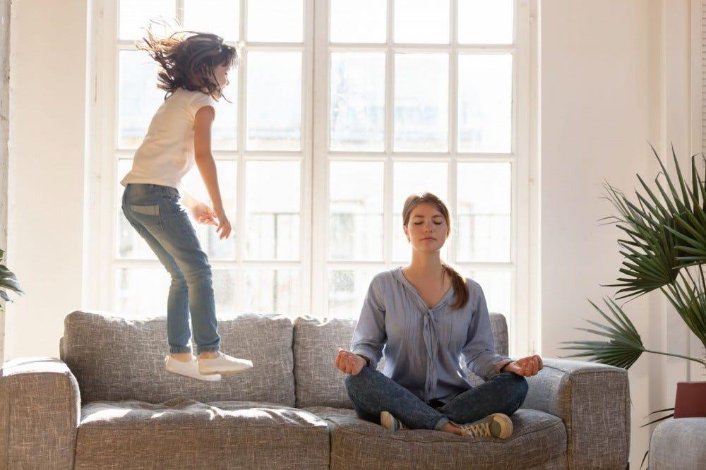 Egy nő meditál, miközben egy kislány ugrik mellé a kanapéra.