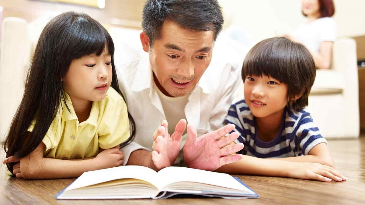 father reading a book to his two children while his wife relaxes nearby, listening