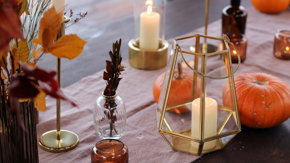 Candles, leaves, pumpkins, and other fall decor on a table.