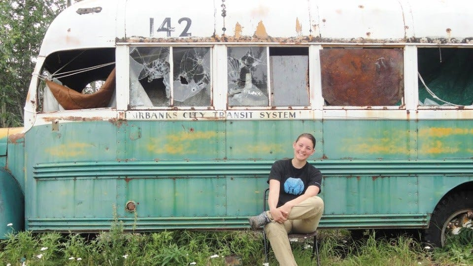 "A woman sitting on a chair in front of the green, yellow, and white bus 142 from ""Into the Wild."""