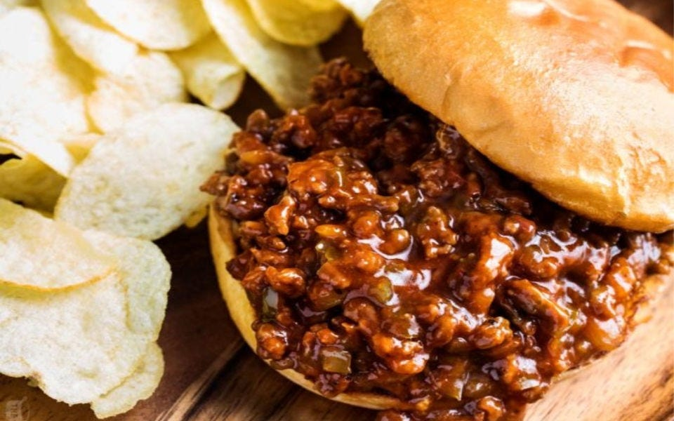 A bun stuffed with homemade sloppy joe meat, with a side of potato chips.