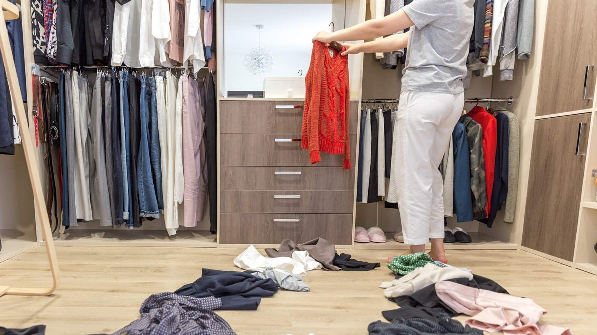 Woman sorting through clothing in her walk in closet.