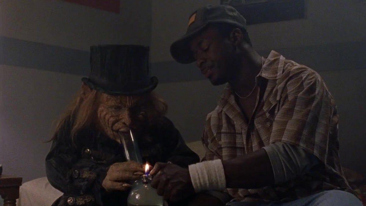 A Leprechaun smoking a bong being a lit by a man sitting next to him.