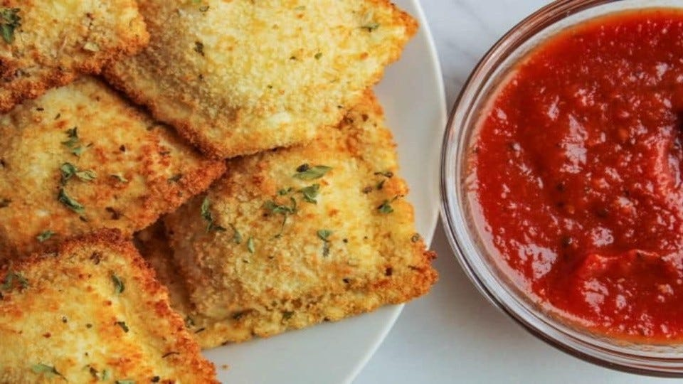 A close-up view of air-fried ravioli with a side of marinara sauce.