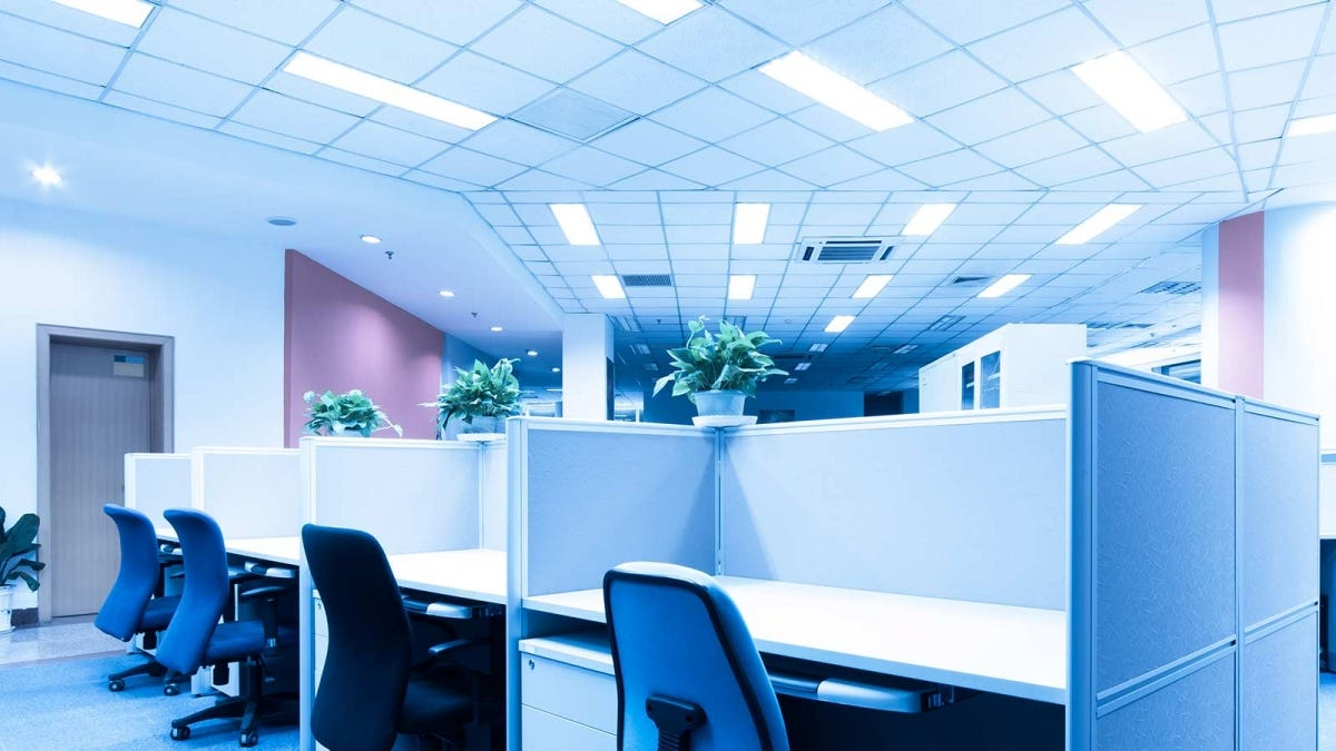 An office with fluorescent ceiling lights and empty cubicles.