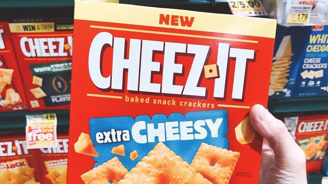 A hand holding a box of extra cheesy Cheez-Its