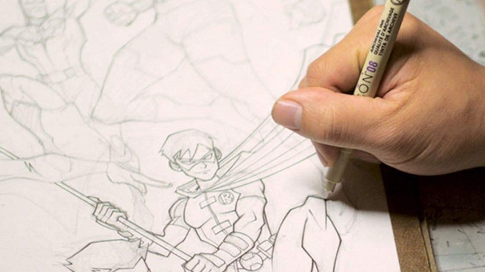 An artist tracing over a pencil drawing using a Sakura Pigma Drawing marker.