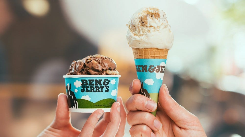 One hand holding a Ben & Jerry's pint of ice cream, and another holding an ice-cream cone in a Ben & Jerry's wrapper.