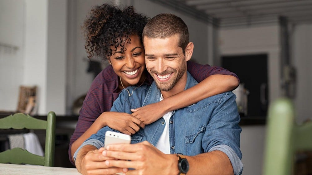 A man and woman looking at an app on a phone and smiling.