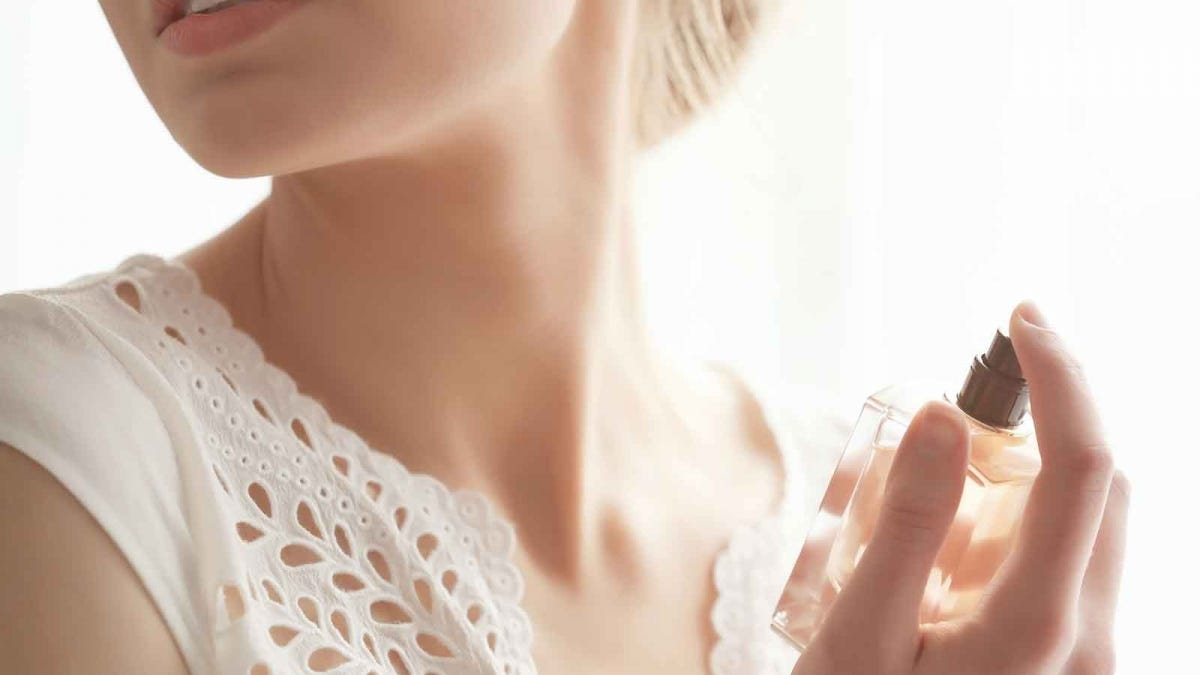 A woman spritzing perfume on her neck.