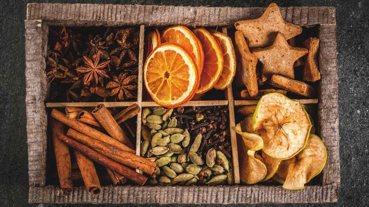 A tray with bins of gingerbread cookies, dried apple, orange, cardamom, cloves, cinnamon, and anise.