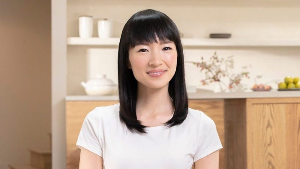 Marie Kondo sits on a bench in front of an organized countertop.