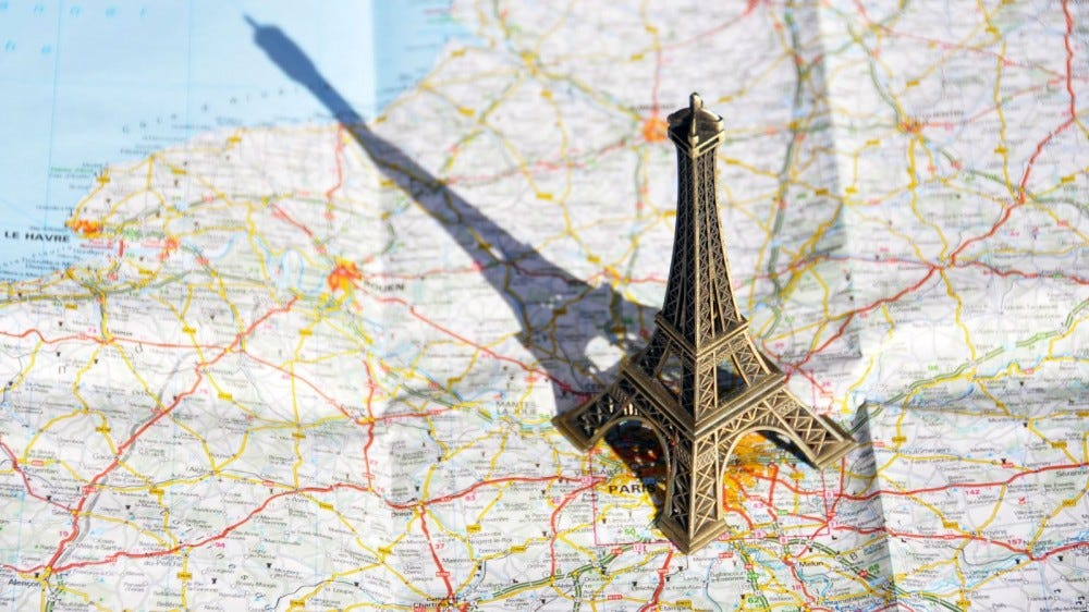 A figurine of the Eiffel Tower sitting on a map of France.